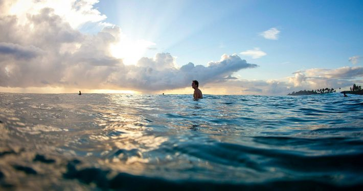 surfer-sitting-waiting-for-waves-calm-sea-water-view