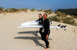 surfing-couple-walking-on-beach-surfboards
