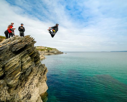 coasteering-guide-mid-air-demonstrating-deep-water-cliff-jump