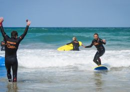 surf-coach-celebrating-success-student-standing-up-surfing