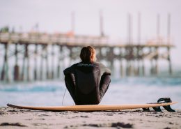 surfer-sitting-next-to-surfboard-beach